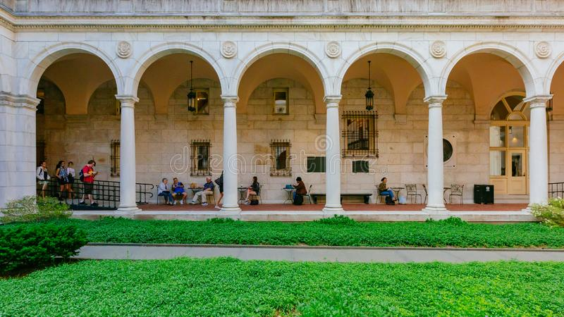 View of arched corridor and inner courtyard of Boston Public Library, where locals rest or gather stock images