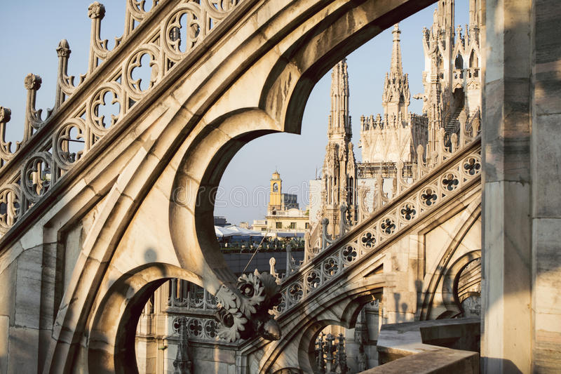 View through the arches and spires of the gothic cathedral Duomo di Milano, Italy. View of Milan through the arches, pinnacles and spires of the adorned gothic stock image