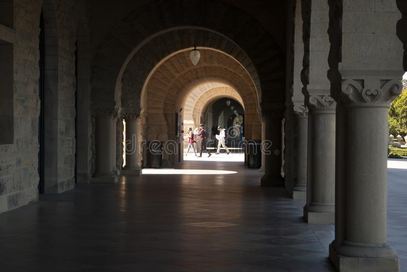View through the arches on youth people walking stock photo