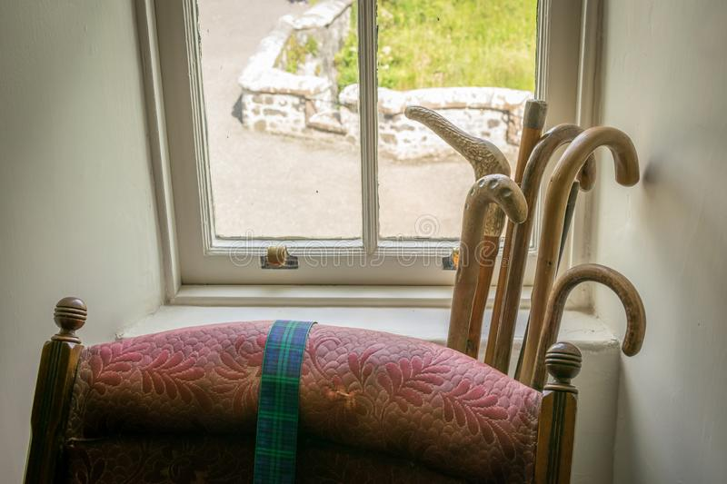 A view of an arm chair with a bunch of walking sticks behind it, in a window bay area. Vintage walking sticks behind an antique armchair royalty free stock photo