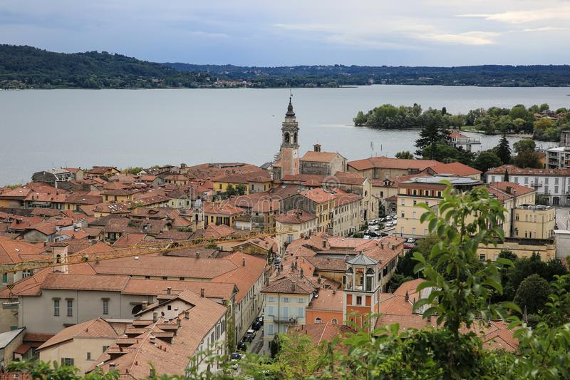 View at Arona and Lake Maggiore, Italy. Medieval city, cathedral, blue sky with clouds, September, autumn stock photo