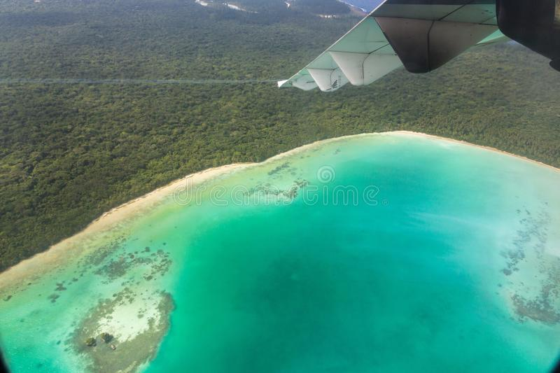 View of wing, azure lagoon and yellow sandy beach from an airplane window, Isle of Pines, New Caledonia. Oceania. royalty free stock photography