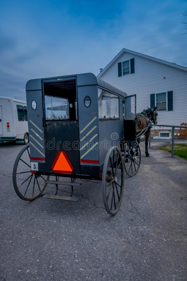 View of the back of Amish buggy with a horse parked in a farm stock photography