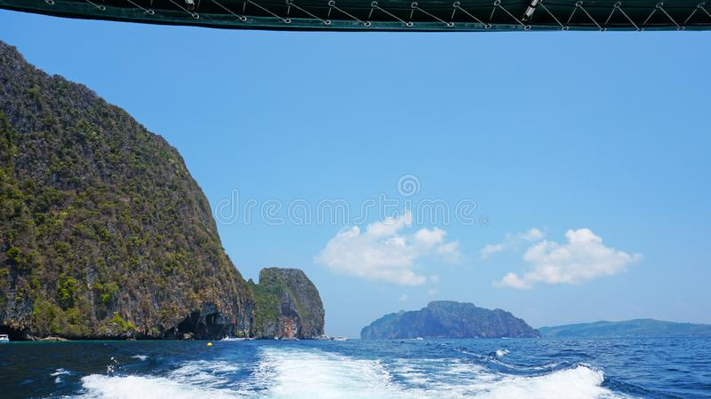 View of the back of the boat. Waves from the engines of a high-speed boat. It offers a landscape of Islands, sea, green hills and blue sky. White clouds hung royalty free stock image