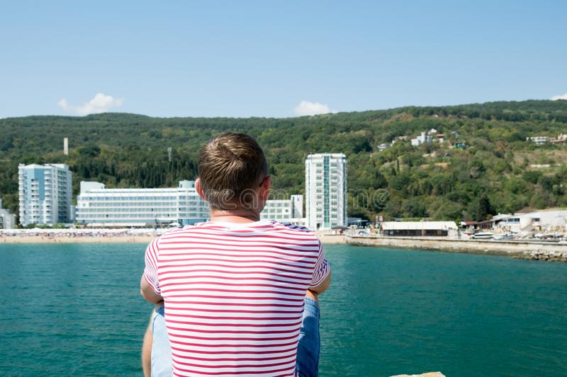 Fair-haired man looks at the sandy beach and marina. View from the back, a fair-haired man in a beach striped t-shirt looks at the sandy beach and waterfront stock image
