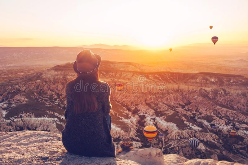 A view from the back of a girl in a hat sits on a hill and admires the beautiful view. A girl in a hat on top of a hill in silence and loneliness admires the royalty free stock photo