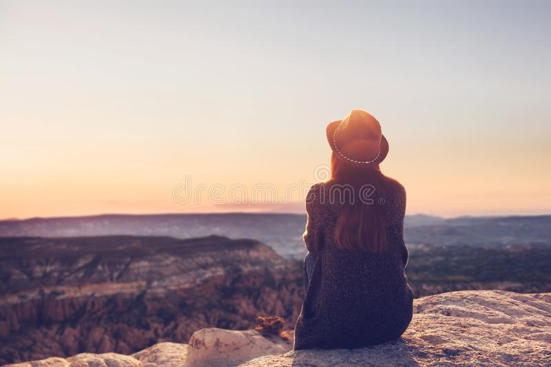 A view from the back of a girl in a hat sits on a hill and admires the beautiful view. A girl in a hat on top of a hill in silence and loneliness admires a stock images