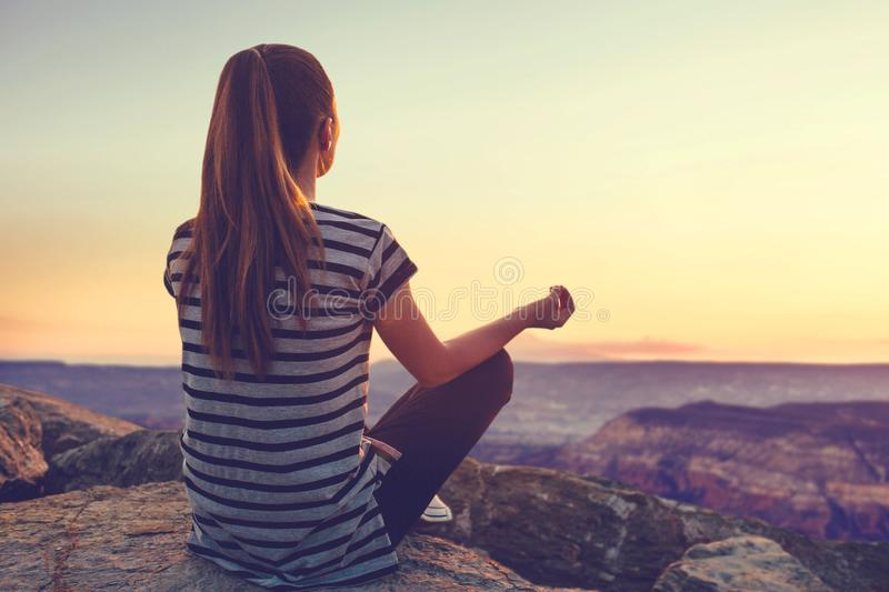 A view from the back of a girl sits on a hill. A girl on top of a hill in silence and loneliness admires a tranquil natural landscape in search of a soul. Or royalty free stock photos