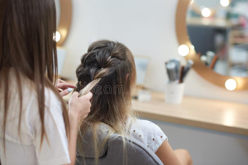 View from back of hairdresser braiding two spikelets to client in beauty salon stock image