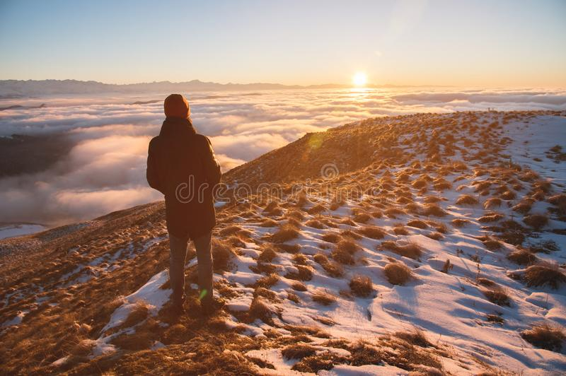 View From the back. A lonely standing man high in the mountains looks at the setting sun and the sunset horizon with a royalty free stock photos