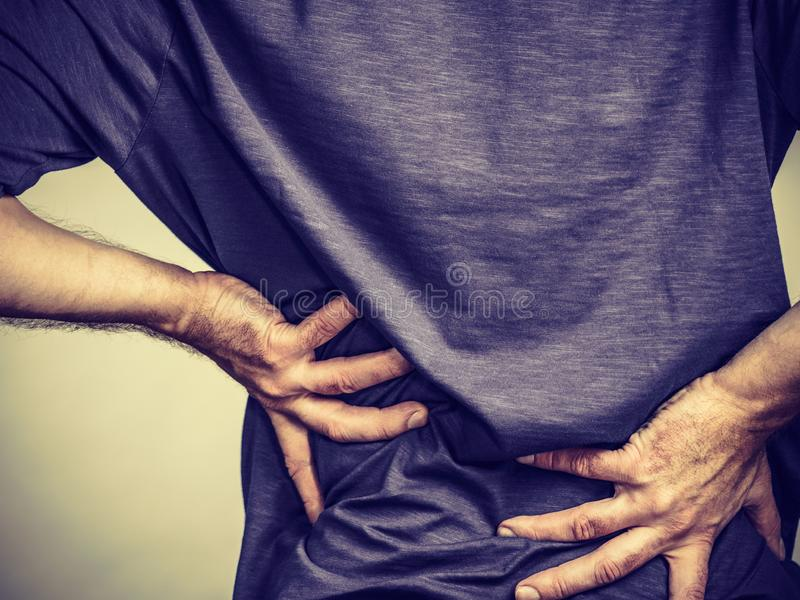 Man having back loins pain ache. View from back on man having terrible loins pain ache. Guy suffering from health problem stock photo