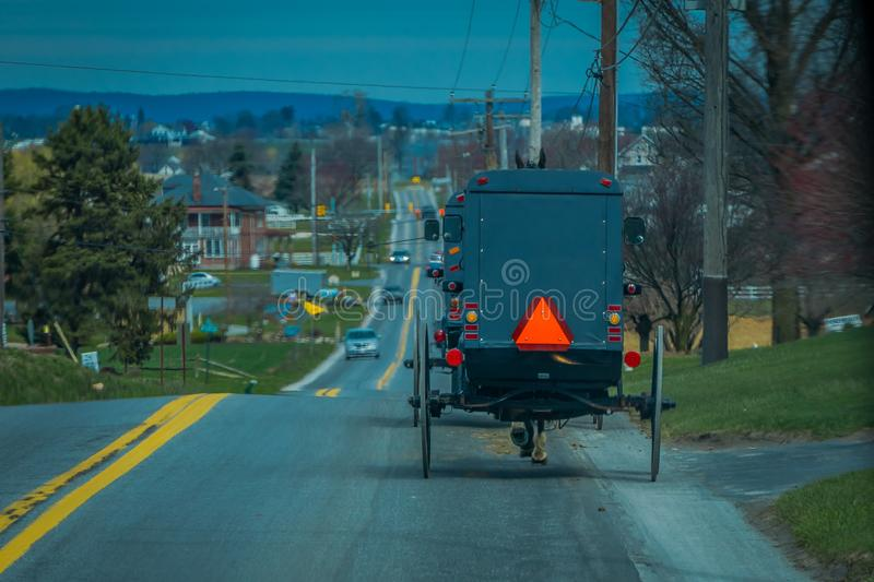 View of the back of an old fashioned, Amish buggy with a horse riding on gravel rural road royalty free stock image