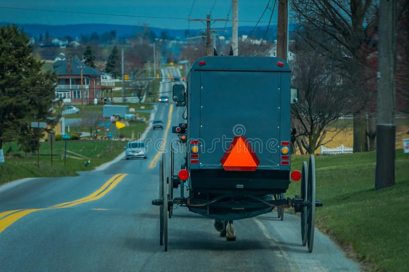 View of the back of an old fashioned, Amish buggy with a horse riding on gravel rural road royalty free stock photo