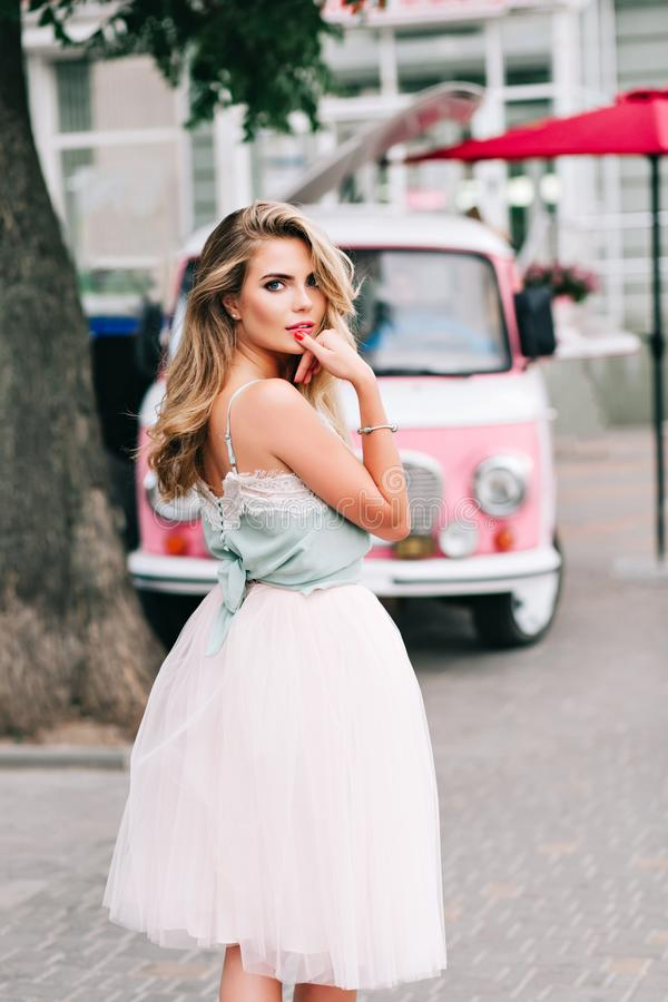 View from back pin up styled girl with long blonde hair on pink retro car background. She wears light tulle skirt, blue royalty free stock photo