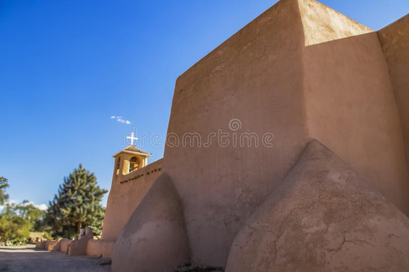 View from back and side of the San Francisco de Asis Mission Church in Taos New Mexico showing one bell tower with cross and birds royalty free stock photo