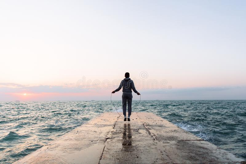 View from back on sportsman jumping with skipping rope, on pier. Full length view of young man in sportswear jumping with skipping rope, workout on pier, near stock image