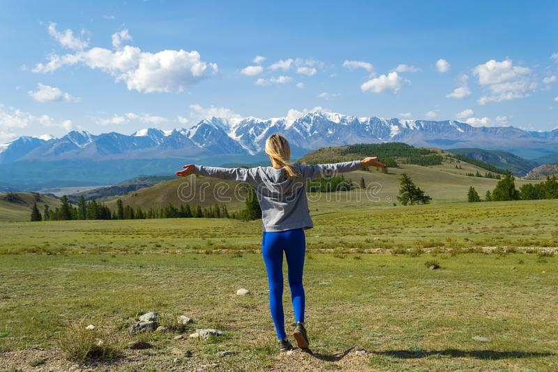 View from the back to the blond tourist girl standing on mountain resting and arms outstretched,against of snow-capped Altai mo. Untains and blue sky with white royalty free stock photos