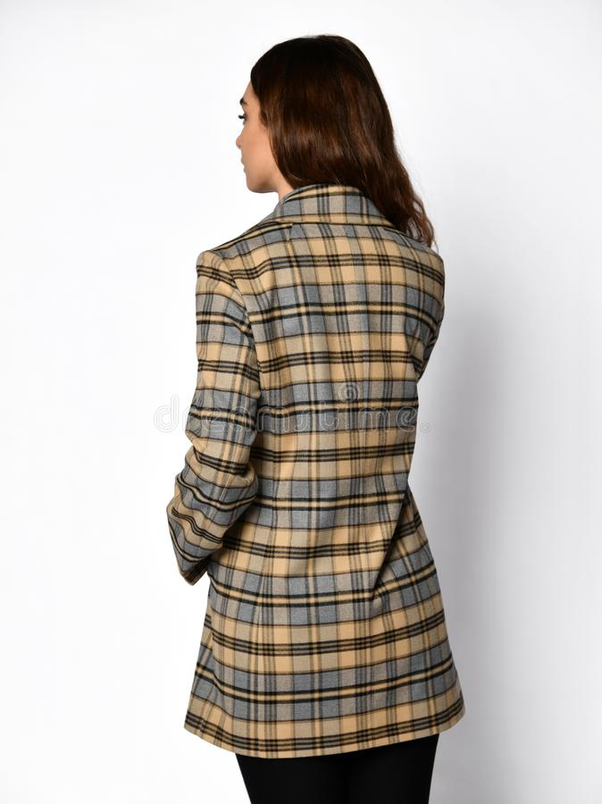 The view from the back. Young beautiful woman posing in checked fashion casual jacket stock image
