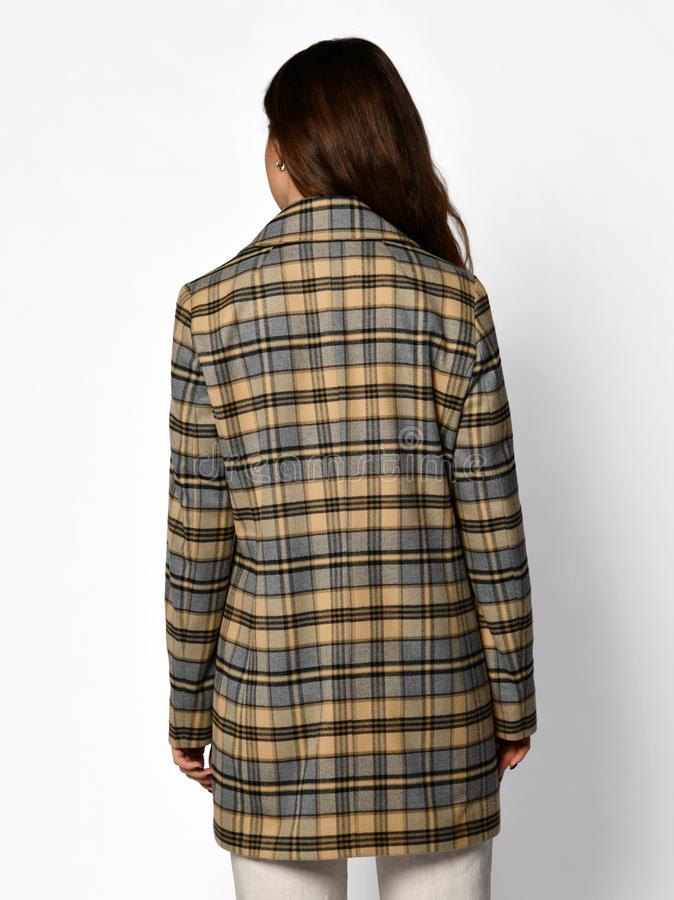 The view from the back. Young beautiful woman posing in checked fashion casual jacket and white trousers stock image