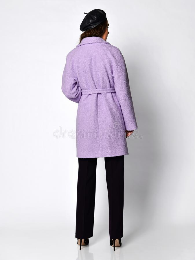 The view from the back. Young beautiful woman posing in new medium length fashion casual pink winter coat, beret and trousers stock photo