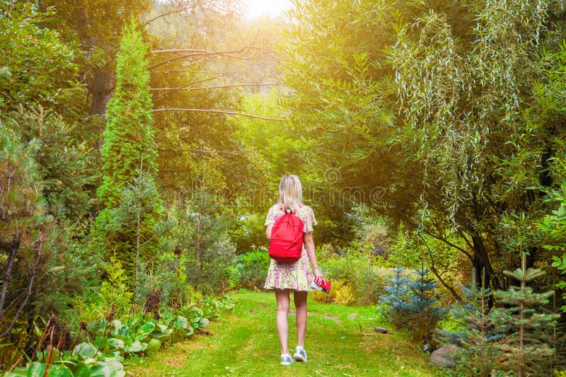 A view from the back of a young blonde girl in a yellow dress with a red backpack on her back, a phone, map in hand walks along a. Path in a park or forest at stock photography