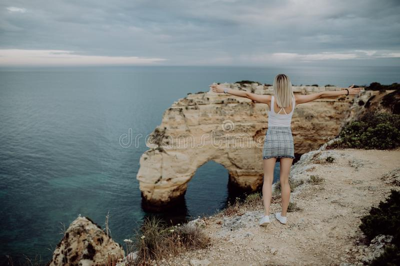 View from the back. A young woman tourist enjoys the beautiful views of the Atlantic Ocean and the landscape off the coast in Port royalty free stock images