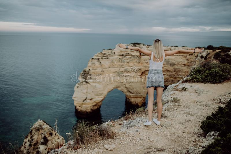 View from the back. A young woman tourist enjoys the beautiful views of the Atlantic Ocean and the landscape off the coast in Port stock photo