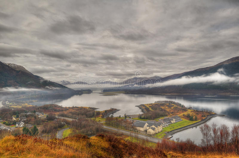 View on Ballachulish and Loch Leven, Scotland. View on the Loch Leven valley and Ballachulish village. Low clouds reflecting in the lake under a dramatic sky stock photo