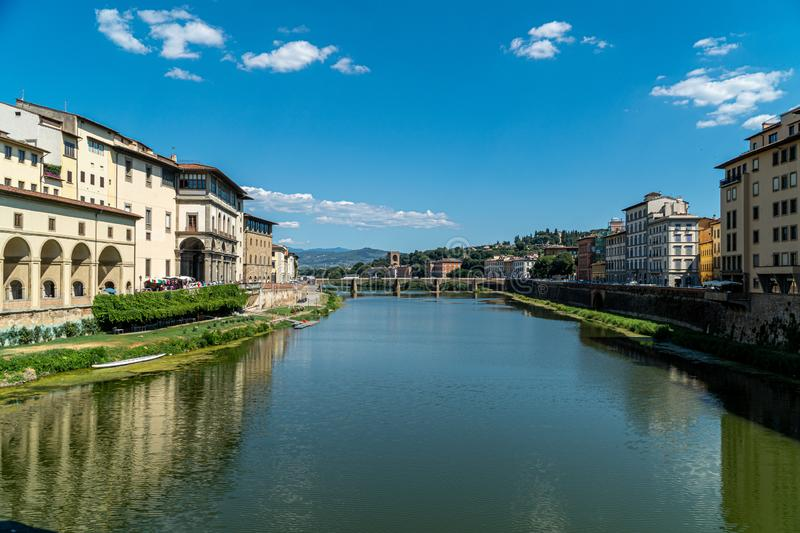 View on the banks of the Arno. With the reflections of these in the water in the middle of a sunny summer`s day royalty free stock image
