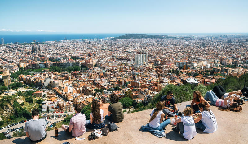 View of Barcelona, the Mediterranean sea, Sagrada Familia, Catalonia, Spain. Barcelona, Catalonia, Spain - May 30, 2015: Young people sit on the viewpoint royalty free stock photo