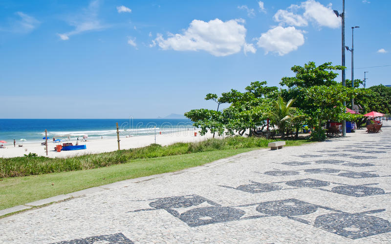 View of Barra da Tijuca beach with palms and mosaic of sidewalk. In Rio de Janeiro. Brazil royalty free stock photography
