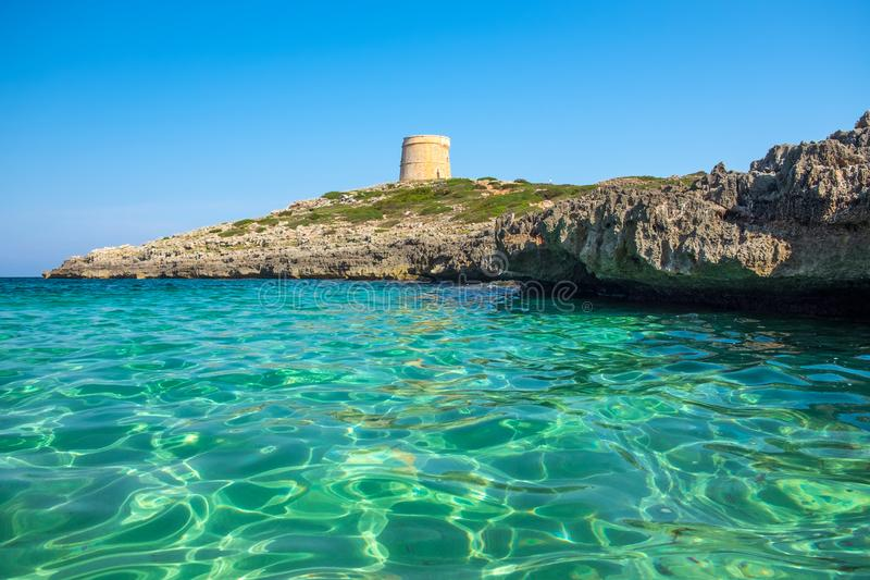 View on the beach Calo Roig with crystal water and the Defense Tower Alcaufar on Menorca stock photo