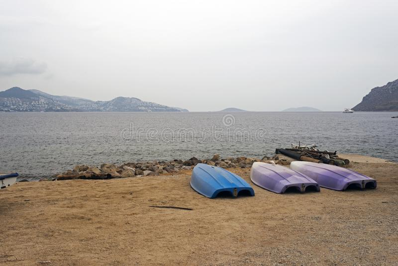 A view of a beach and canoes in a cloudy weather in Bodrum, Turkey.  royalty free stock photo