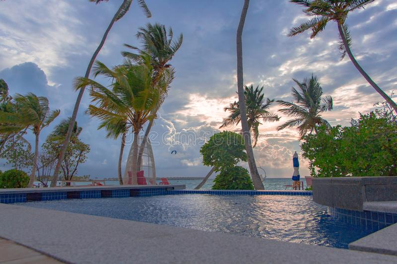 A view of the beach during a cloudy sunset overlooking from swimming pool stock photos