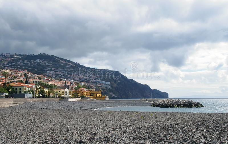 View of the beach at funchal with coastal city buildings and surrounding hills stock image