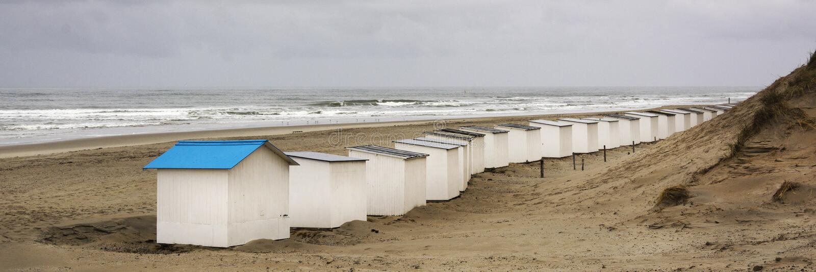 View on the beach huts on the west coast area of Texel. Panoramic view on the North Sea. On a day in autumn with beautiful waves and a heavy grey sky, Typical stock image