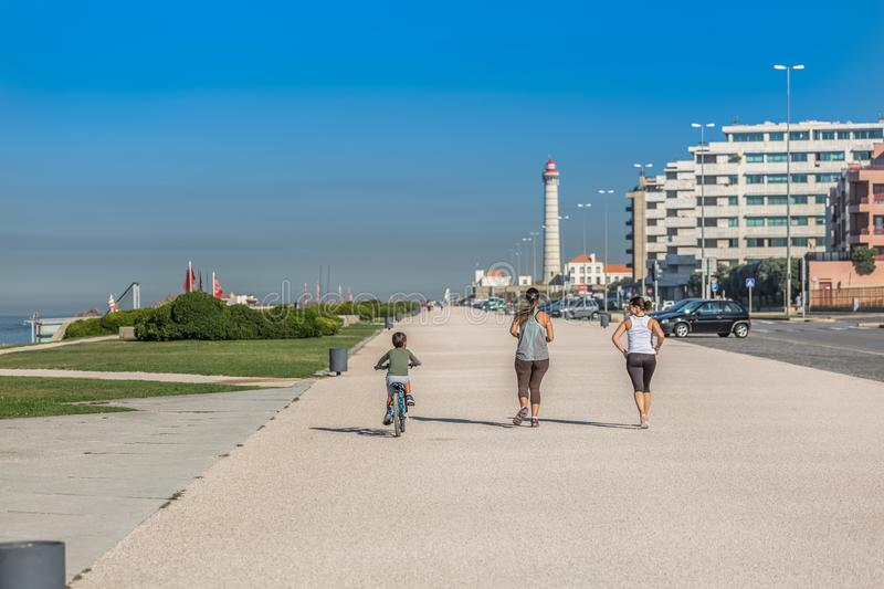View of the beach of Leca da Palmeira, with people doing exercise and walking, on coast next to the beach, lighthouse in the royalty free stock image