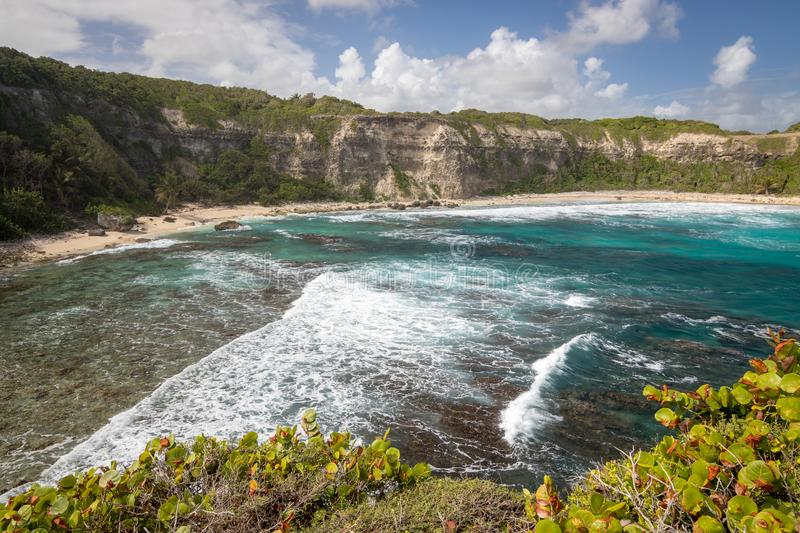 View at beautiful bay with big waves in Guadeloupe - Plage de la Porte d`Enfer du Moule Beach at Gate to Hell by town Moule royalty free stock photo