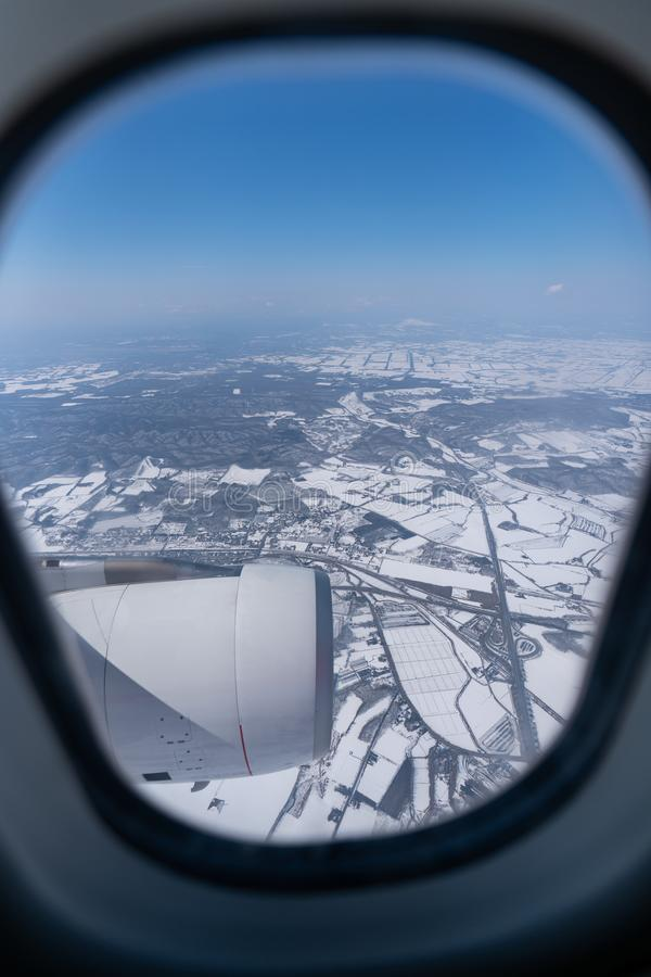 View of beautiful city covered by snow from a airplane window royalty free stock image