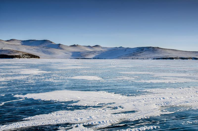 View of beautiful drawings on ice from cracks and bubbles of deep gas on surface of Baikal lake in winter, Russia. View of beautiful drawings on ice from cracks royalty free stock photography