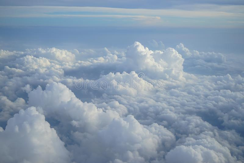 View of beautiful free form dense white cloud with shades of blue sky background from flying plane window. In morning sunrise stock photo