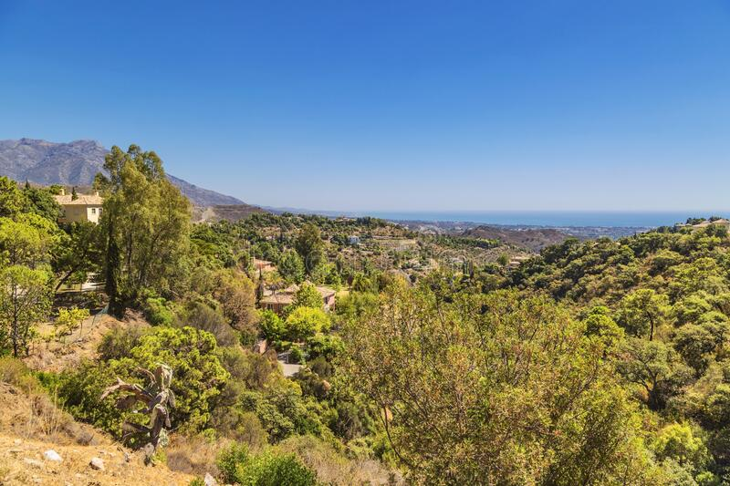 View of a beautiful hillside with the sea and mountains royalty free stock images