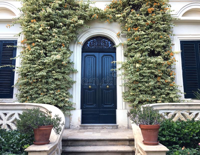 View of a Beautiful House Exterior and Front Door Seen. There are windows on either side of the door, plants on the wall stock images
