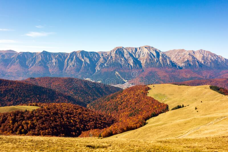 View of beautiful mountain peaks rising above the colored forest stock photography