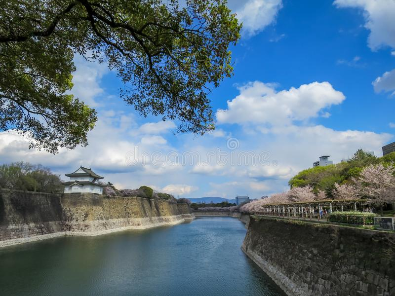 View of beautiful Osaka castle stone bank moat through green tree branches with cherry blossom row and blue sky background stock images