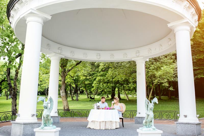 Royal alcove with couple in the garden. View on the beautiful royal alcove with couple having romantic breakfast in the garden stock images