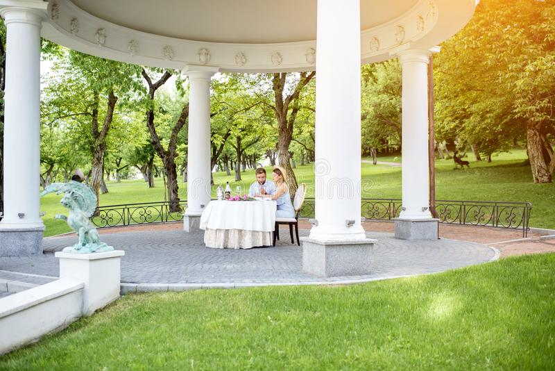 Royal alcove with couple in the garden. View on the beautiful royal alcove with couple having romantic breakfast in the garden stock photography