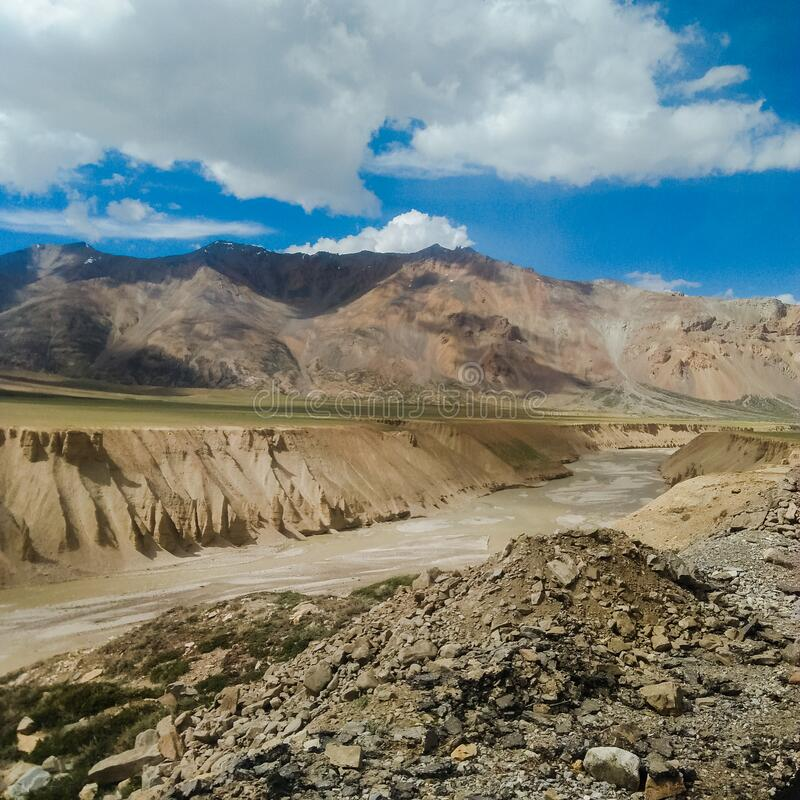 View of beautiful sandy mountains and snowing water river with lovely sky in tourism of leh ladakh. India stock photo