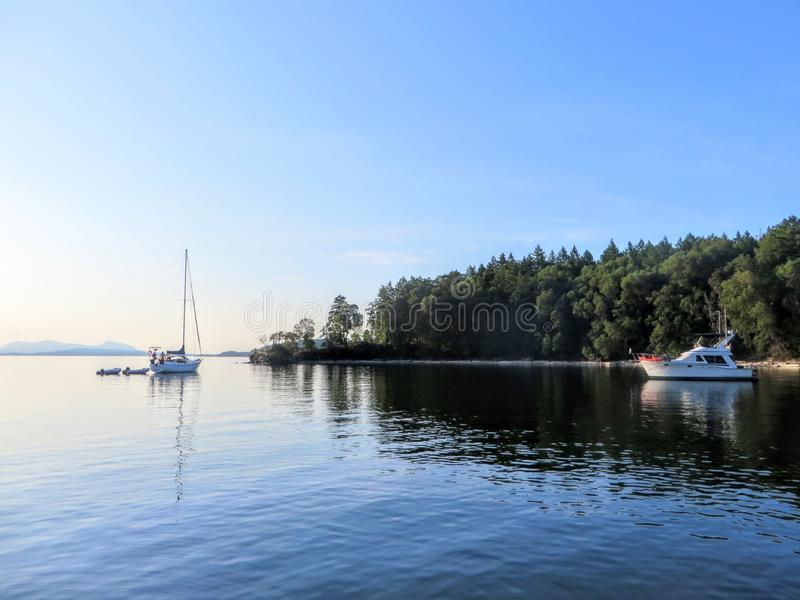A view of a beautiful secluded bay during a beautiful sunny evening.  The water is calm, a few boats are anchored, royalty free stock image