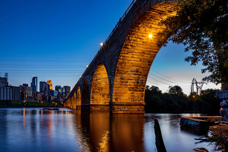A view of the beautiful stone arch bridge of Minneapolis, MN, USA at dusk. Showing part of the city skyline stock photography